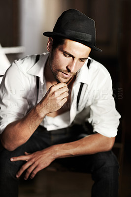 Buy stock photo A handsome young man sitting and looking down