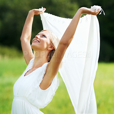 Buy stock photo Smiling young woman holding up a piece of white linen