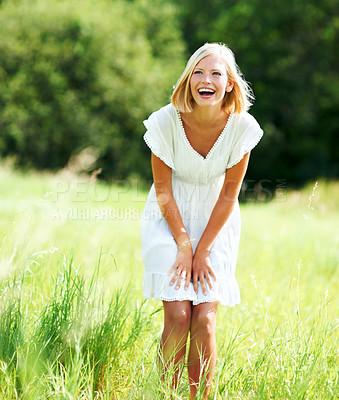 Buy stock photo Cute young woman laughing while standing in a field outdoors