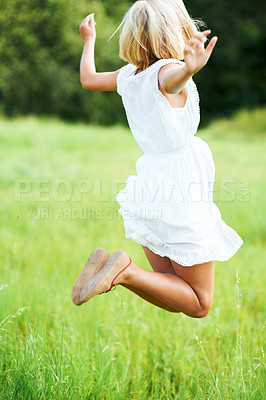 Buy stock photo Beautiful young woman jumping while in a field outdoors