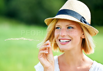 Buy stock photo Happy young woman smiling while wearing a hat and chewing a wheat stalk