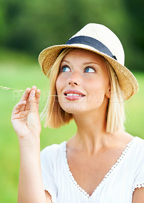 Buy stock photo Attractive young woman smiling while wearing a hat and chewing a wheat stalk