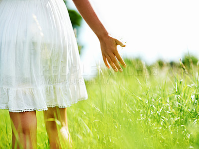 Buy stock photo Cropped view of a young woman walking through a green field