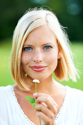 Buy stock photo Gorgeous young woman holding a tiny flower outdoors