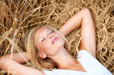 Buy stock photo Lovely young woman lying in a field of wheat