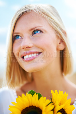 Buy stock photo Positive young woman holding some sunflowers while outdoors