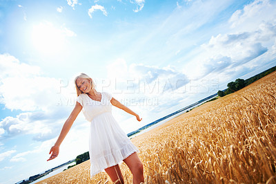 Buy stock photo Happy young woman walking through a wheat field