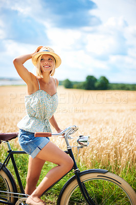 Buy stock photo Lovely young woman riding a bicycle in the countryside