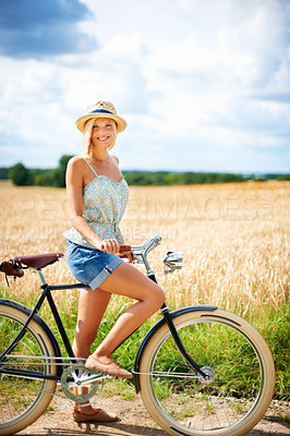 Buy stock photo Pretty young woman riding a bicycle in the countryside