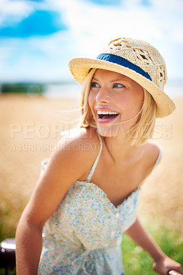Buy stock photo Laughing young woman standing with her bicycle in the countryside