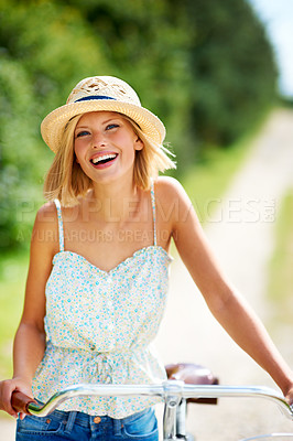 Buy stock photo Positive young woman walking alongside her bicycle in the countryside