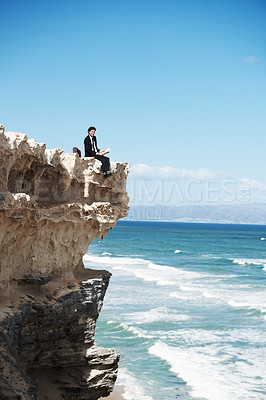 Buy stock photo Young businessman sitting on the edge of a cliff overlooking the ocean and reading a book