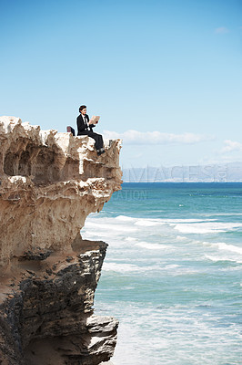 Buy stock photo Attractive businessman sitting on the edge of a cliff overlooking the ocean and reading a book