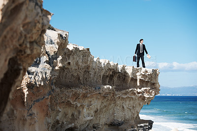 Buy stock photo Businessman standing on the edge of a cliff looking out over the ocean while holding a briefcase