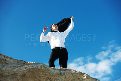 Buy stock photo Low-angle view of happy businessman standing on a rock with his hands in the air in a gesture of victory
