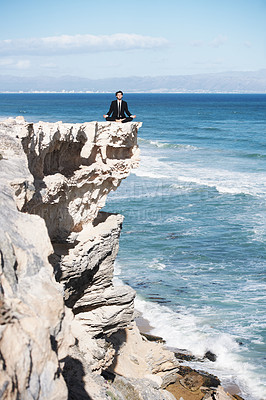 Buy stock photo Businessman sitting and meditating on top of a cliff above the ocean