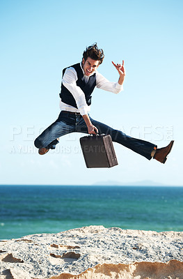 Buy stock photo Happy young businessman jumping in the air holding a briefcase with the ocean in the background