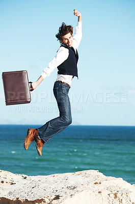 Buy stock photo Young man holding a briefcase and jumping in the air with the ocean in the background