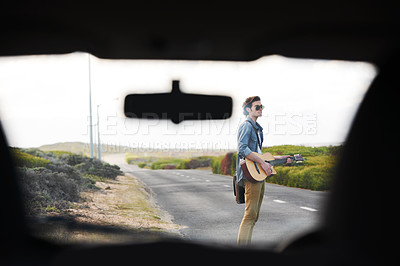 Buy stock photo Young man with a guitar on the roadside seen through the windshield of a car