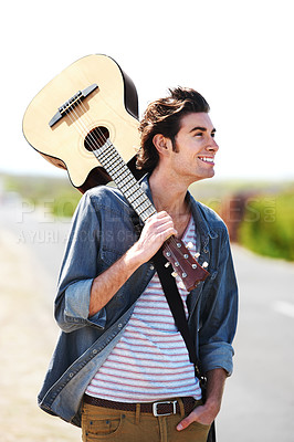 Buy stock photo Smiling young man holding his guitar over his shoulder standing on the side of the road - closeup