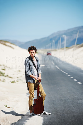 Buy stock photo Trendy young man standing waiting on the side of the road with a guitar