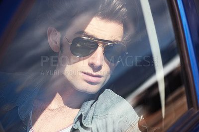 Buy stock photo Closeup of a handsome young man seen through the window of a car with reflections in the foreground