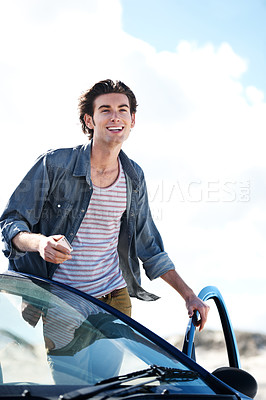 Buy stock photo Happy young man holding a cellphone and leaning on the roof of his car while smiling