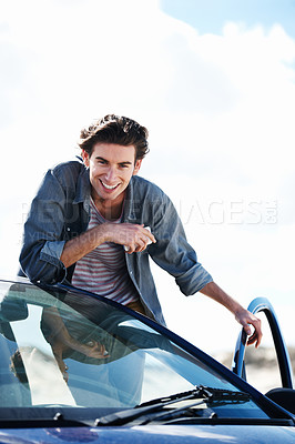 Buy stock photo Happy young man holding a cellphone and leaning on the roof of his car while smiling at the camera