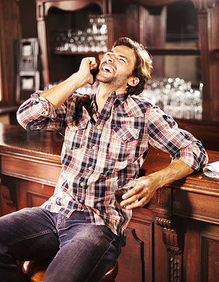 Buy stock photo Handsome young guy perched at a bar counter with a drink in hand while making a call on his mobile