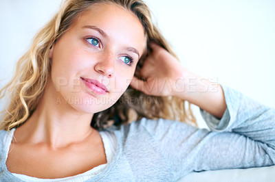 Buy stock photo A pretty young woman working looking away thoughtfully while working on her laptop at home