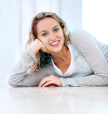Buy stock photo A cute young blonde lying on the floor and smiling at you