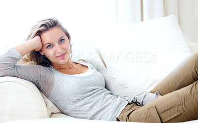 Buy stock photo Portrait of a young woman relaxing on her couch at home