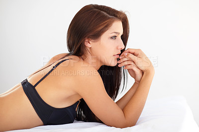 Buy stock photo A beautiful young woman lying on her bed wearing black lingerie