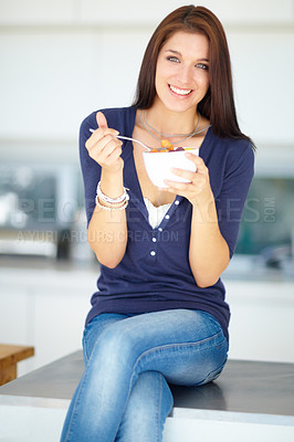 Buy stock photo Portrait of a smiling young woman eating a healthy fruit salad for lunch