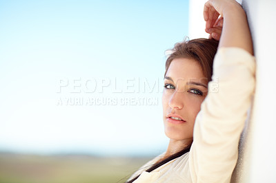 Buy stock photo Portrait of a beautiful young woman leaning in a white wall outside