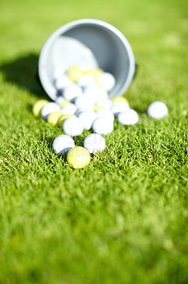 Buy stock photo Shot of a bucket of golf balls on a golf course