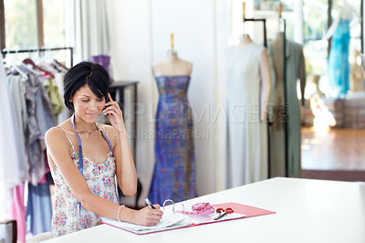 Buy stock photo A beautiful young ethnic woman making appointments via cellphone