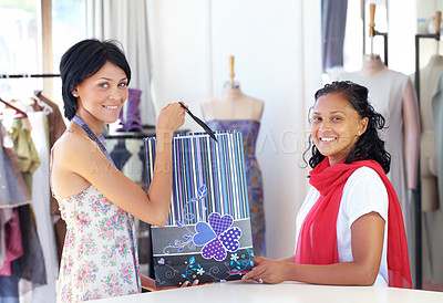 Buy stock photo An attractive young ethnic woman handing over a package to a customer