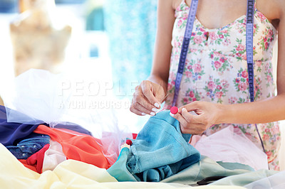 Buy stock photo Cropped image of a woman's hands sewing a button to a garment at work