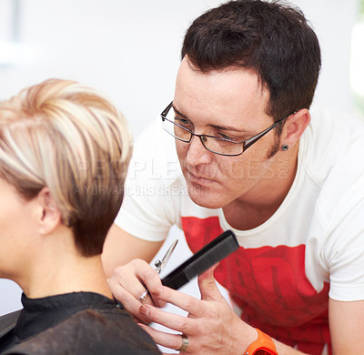 Buy stock photo A hairdresser putting the final touches on his client's head