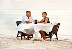 Lovely mature couple sitting at the seaside dinning table
