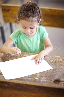 Buy stock photo Sweet little girl sitting at a school desk and drawing