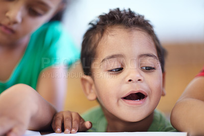 Buy stock photo Cute little boy looking at a drawing while at a table