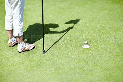 Buy stock photo Cropped view of a mature lady standing on a putting green holding a flag next to a hole and golf ball
