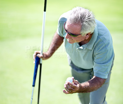 Buy stock photo A senior man holding a golf ball and his putter and flag after making birdie