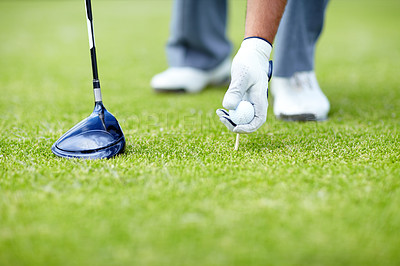 Buy stock photo A male golfer placing his golf ball and tee in the ground