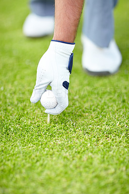 Buy stock photo A male golfer wearing a white golve and placing his golf ball and tee in the ground
