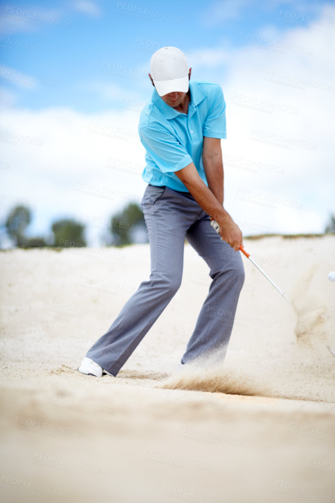 Buy stock photo An image of a young male golfer chipping his ball out of a bunker in a game of golf