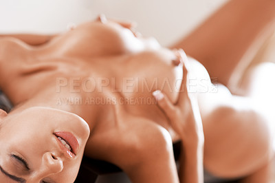 Buy stock photo A sensual nude woman lying on top of a table while holding her breasts