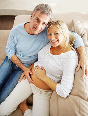 Buy stock photo Top view of a relaxed mature man sitting at home with his pretty pregnant wife, smiling up at the camera